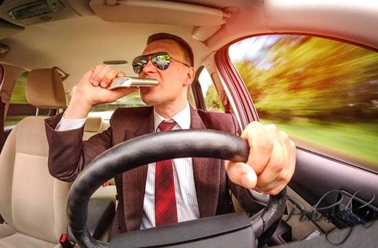 мужчина пьет за рулем автомобиля